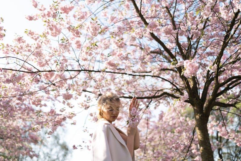 Den h?rliga blonda unga kvinnan i Sakura Cherry Blossom parkerar i v?r som tycker om naturen och fri tid under hennes resande royaltyfri bild