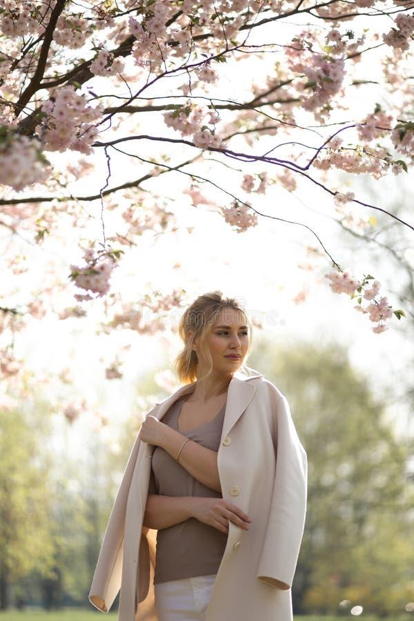 Den h?rliga blonda unga kvinnan i Sakura Cherry Blossom parkerar i v?r som tycker om naturen och fri tid under hennes resande arkivbilder