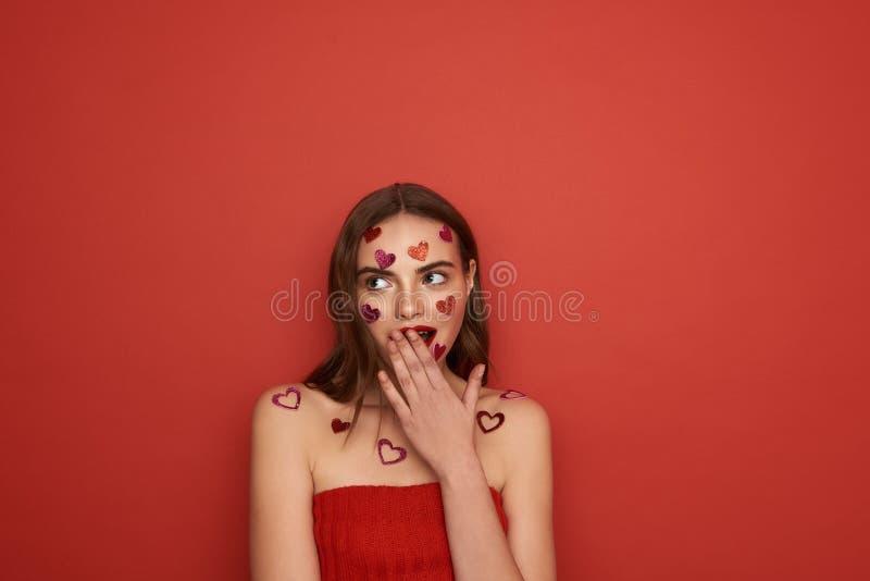 Den h?rliga Caucasian kvinnan dekoreras med r?da hj?rta-formade klisterm?rkear p? f?rgbakgrund royaltyfri foto
