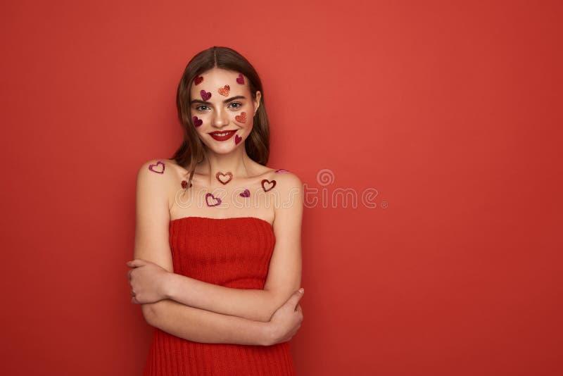Den h?rliga Caucasian kvinnan dekoreras med r?da hj?rta-formade klisterm?rkear p? f?rgbakgrund royaltyfria foton