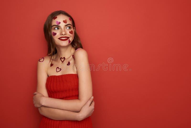 Den h?rliga Caucasian kvinnan dekoreras med r?da hj?rta-formade klisterm?rkear p? f?rgbakgrund arkivbilder