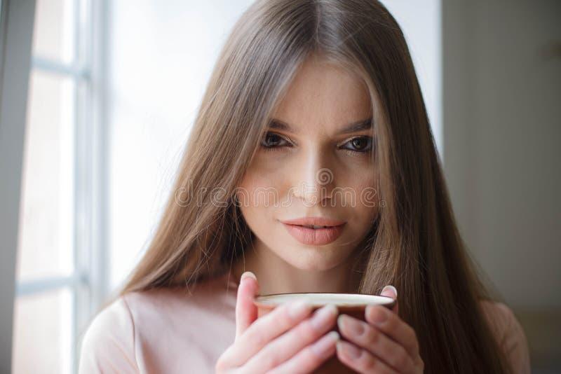 Den h?rliga flickan dricker kaffe och ler, medan sitta p? kaf?t royaltyfri bild