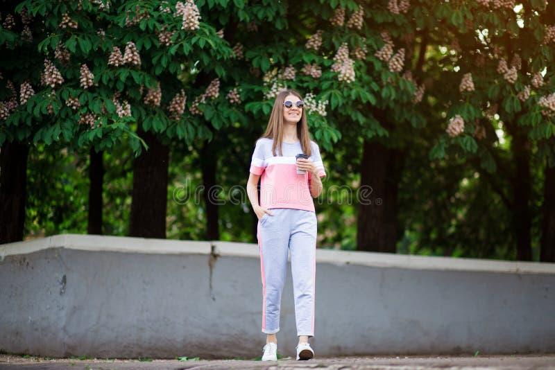 Den h?rliga flickan i solglas?gon g?r vid sommargatan med kaffe arkivfoton