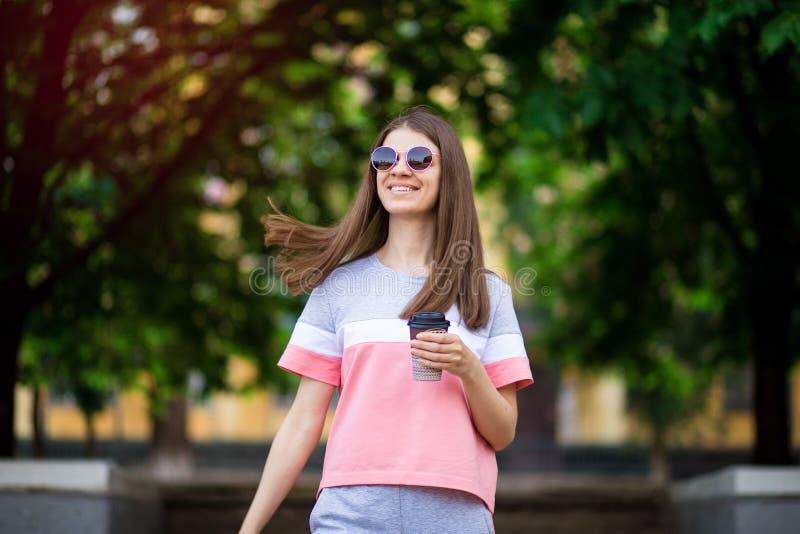 Den h?rliga flickan i solglas?gon g?r vid sommargatan med kaffe royaltyfria bilder