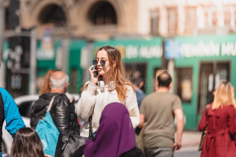 Den h?rliga kvinnan anv?nder smartphonen, medan g? arkivbild