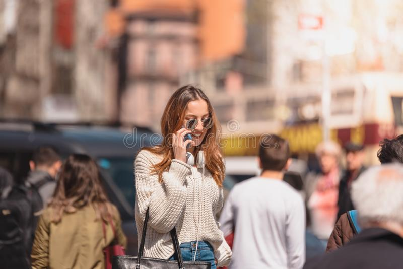 Den h?rliga kvinnan anv?nder smartphonen, medan g? arkivfoto