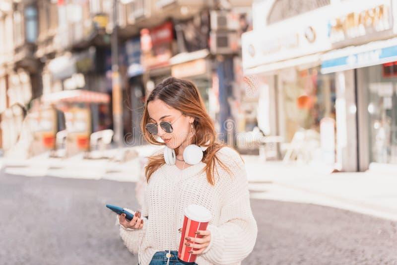 Den h?rliga kvinnan anv?nder smartphonen, medan g? arkivfoton