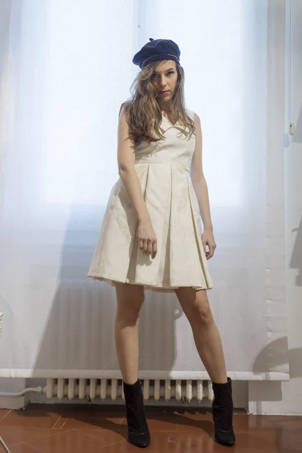 Den h?rliga kvinnan passar p? en vit kl?nning i shoppinggallerian p? en atelier royaltyfria bilder
