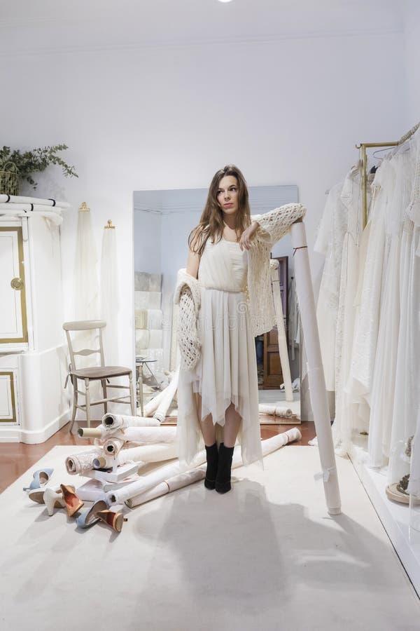 Den h?rliga kvinnan passar p? en vit kl?nning i shoppinggallerian p? en atelier royaltyfri fotografi