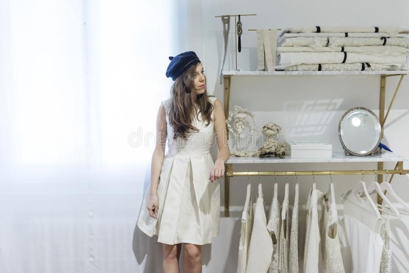 Den h?rliga kvinnan passar p? en vit kl?nning i shoppinggallerian p? en atelier arkivfoton