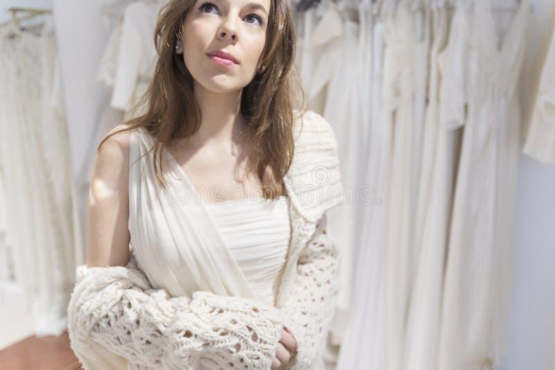 Den h?rliga kvinnan passar p? en vit kl?nning i shoppinggallerian p? en atelier arkivbild