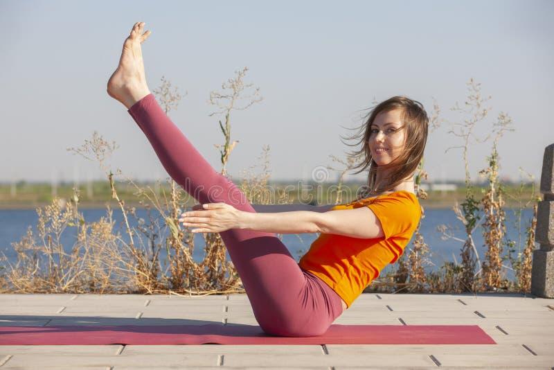 Den h?rliga kvinnan som g?r yoga p? gr?nt gr?s parkerar in, p? sommarmorgonen arkivfoton