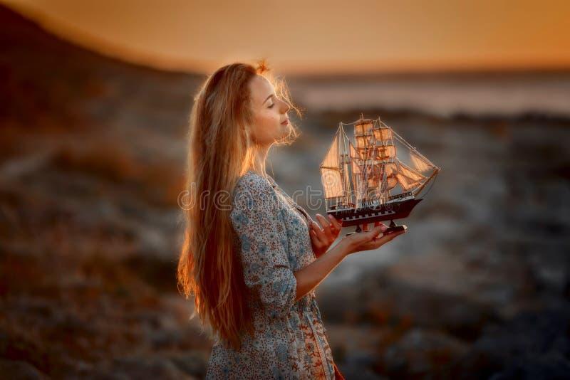 Den h?rliga kvinnan vaggar in kusten p? soluppg?ng arkivbilder