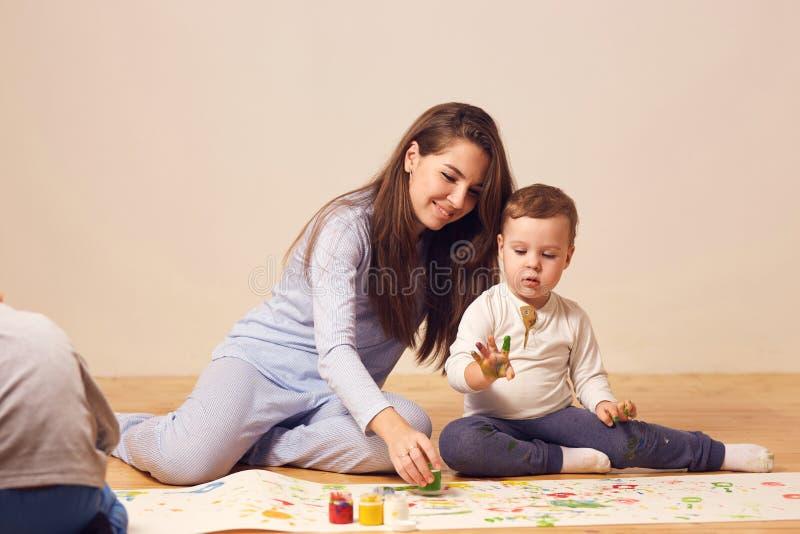 Den h?rliga lyckliga unga modern och hennes ikl?dda hem- kl?der f?r liten son sitter p? tr?golvet i rummet och royaltyfri bild