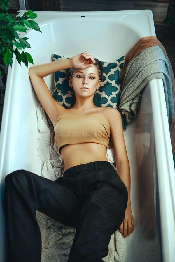 Den h?rliga modellen poserar i ett badrum med id?rikt f?rsilvrar makeup royaltyfri bild