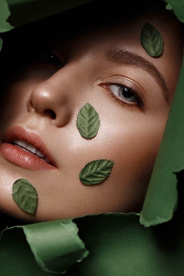 Den h?rliga nya flickan med perfekt hud som ?r naturlig utg?r och gr?na sidor H?rlig le flicka close upp royaltyfri fotografi