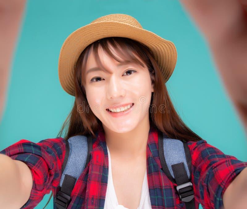 Den h?rliga unga asiatiska kvinnan som tar selfie med kameran f?r, kopplar av i semester som isoleras p? bl? bakgrund royaltyfri foto