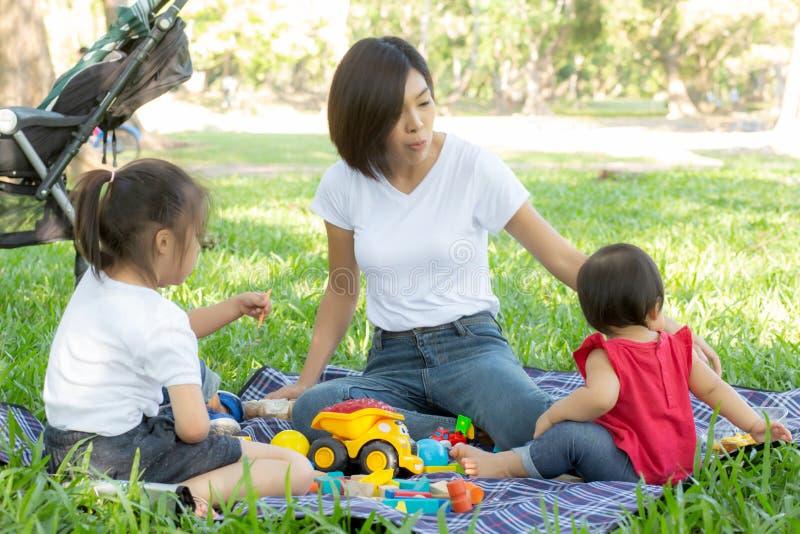 Den h?rliga unga asiatiska mamman och dottern som spelar leksakkvarter f?r att l?ra utveckling som ?r lycklig och som ?r rolig p? royaltyfri foto