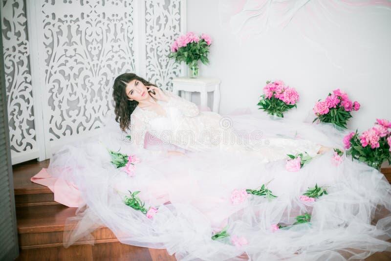 Den h?rliga unga flickan i en vit sn?r ?t kl?nningen med pionblommor royaltyfri bild