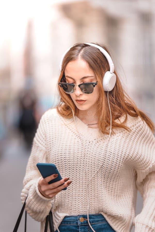 Den h?rliga unga flickan lyssnar musik, medan g? arkivfoto