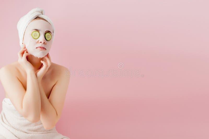 Den h?rliga unga kvinnan applicerar en kosmetisk silkespappermaskering p? en framsida med gurkan p? en rosa bakgrund royaltyfri fotografi