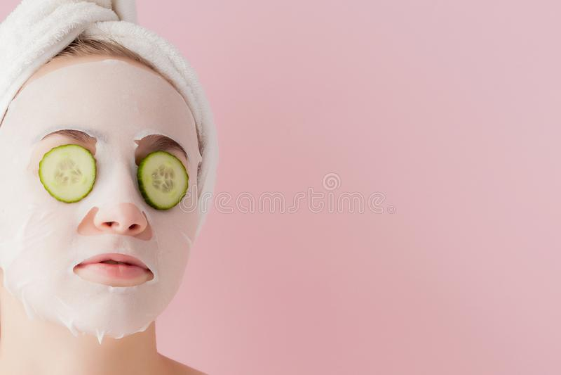 Den h?rliga unga kvinnan applicerar en kosmetisk silkespappermaskering p? en framsida med gurkan p? en rosa bakgrund royaltyfria foton