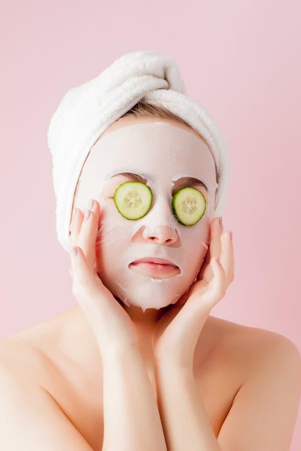 Den h?rliga unga kvinnan applicerar en kosmetisk silkespappermaskering p? en framsida med gurkan p? en rosa bakgrund royaltyfri foto