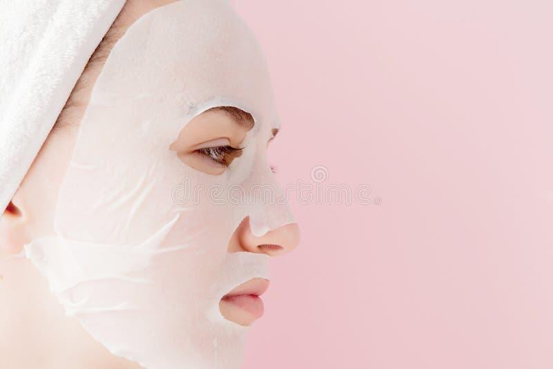 Den h?rliga unga kvinnan applicerar en kosmetisk silkespappermaskering p? en framsida p? en rosa bakgrund Sjukv?rd- och sk?nhetbe arkivfoton