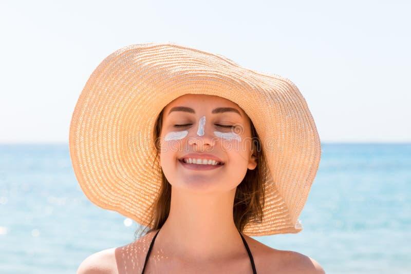 Den h?rliga unga kvinnan i hatt applicerar sunblock under hennes ?gon och p? hennes n?sa som indier Gammal kvinna med hatten och  fotografering för bildbyråer