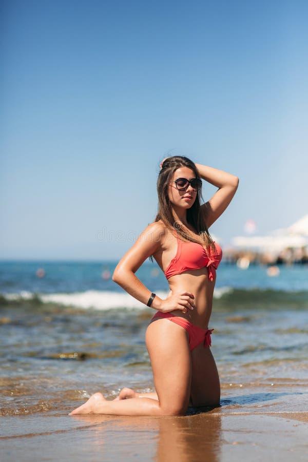 Den h?rliga unga kvinnan med brunetth?r i rosa baddr?kt poserar p? stranden n?ra vaggar p? bakgrunden av havet arkivbilder