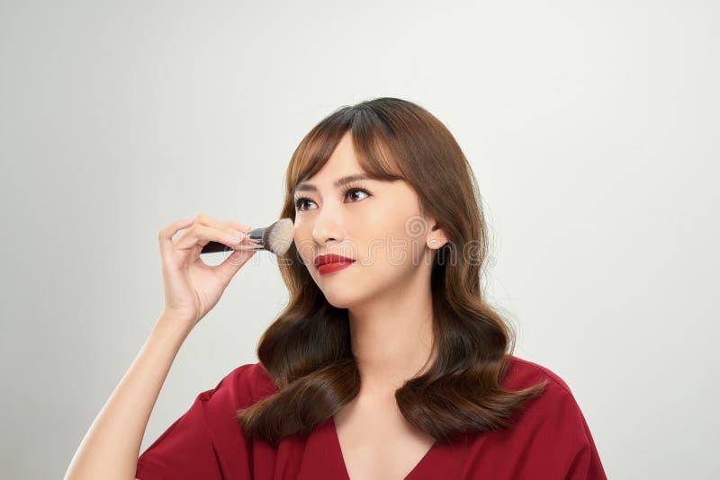 Den h?rliga unga kvinnan som applicerar fundamentet, pudrar, eller rodnaden med makeup borstar royaltyfri bild