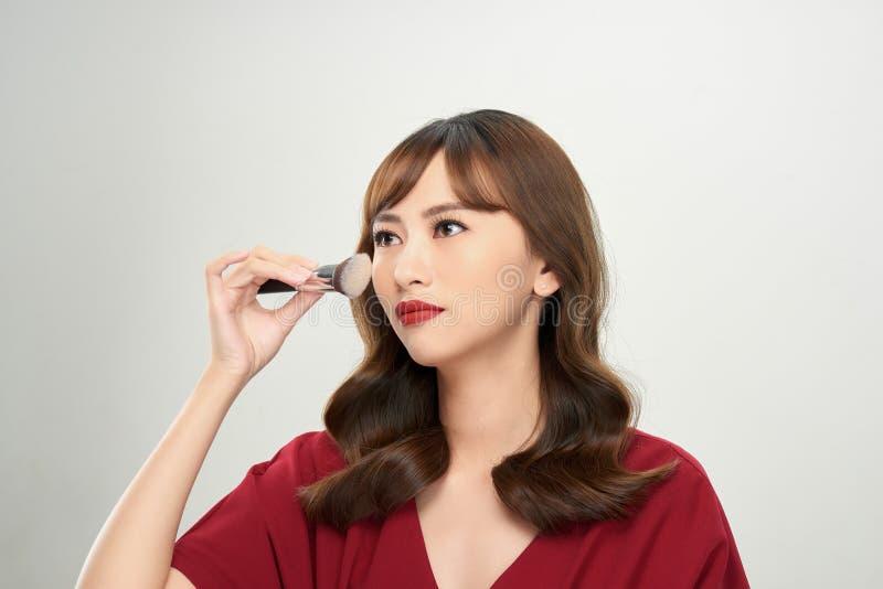 Den h?rliga unga kvinnan som applicerar fundamentet, pudrar, eller rodnaden med makeup borstar arkivfoto