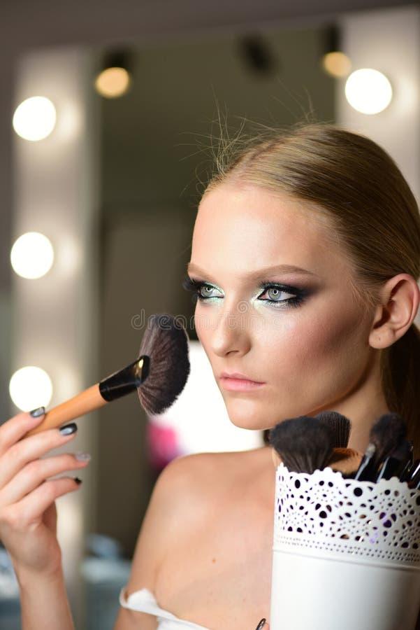 Den h?rliga unga kvinnan som applicerar fundamentet, pudrar, eller rodnaden med makeup borstar arkivfoton