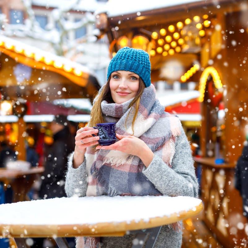 Den h?rliga unga kvinnan som dricker varm stansmaskin, funderat vin p? tysk jul, marknadsf?r Lycklig flicka i vinterkl?der med arkivbilder