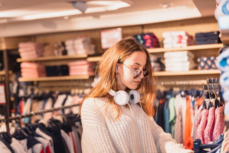 Den h?rliga unga kvinnan v?ljer kl?der p? mode, och kl?der shoppar arkivfoton