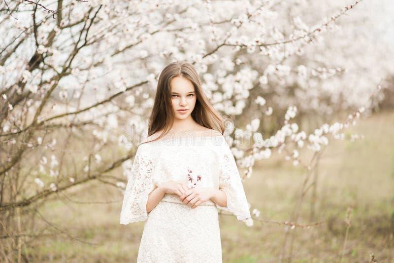 Den h?rliga unga mjuka flickan i blomningtr?dg?rden p? en v?rdag, blommakronblad som faller fr?n tr?det, st?ngde hennes ?gon och  royaltyfri bild
