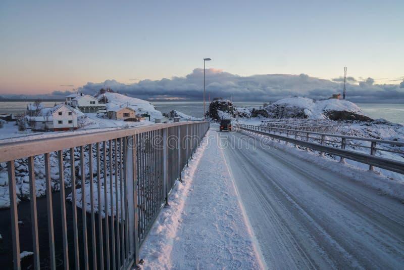 Den hala snöig vägen stöter ihop med bron i Lofoten öar, Norge arkivbilder