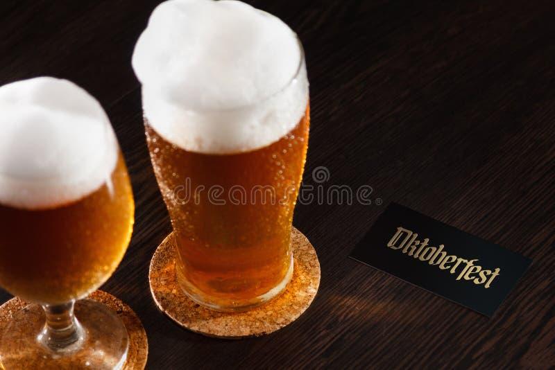 Den halv literen för ölexponeringsglas på en träbakgrund med skum och Oktoberfest smsar arkivfoto