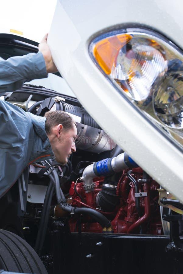 Den halva lastbilsföraren kontrollerar den funktionsdugliga motorn av den vita stora riggen royaltyfri fotografi