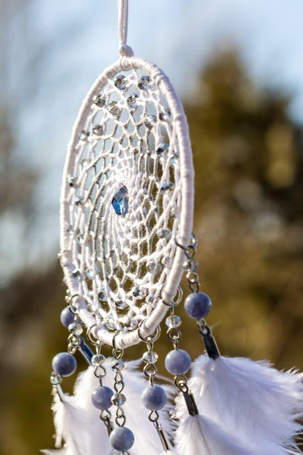 Den handgjorda dröm- stopparen med fjädrar dragar och pryder med pärlor att hänga för rep royaltyfri bild