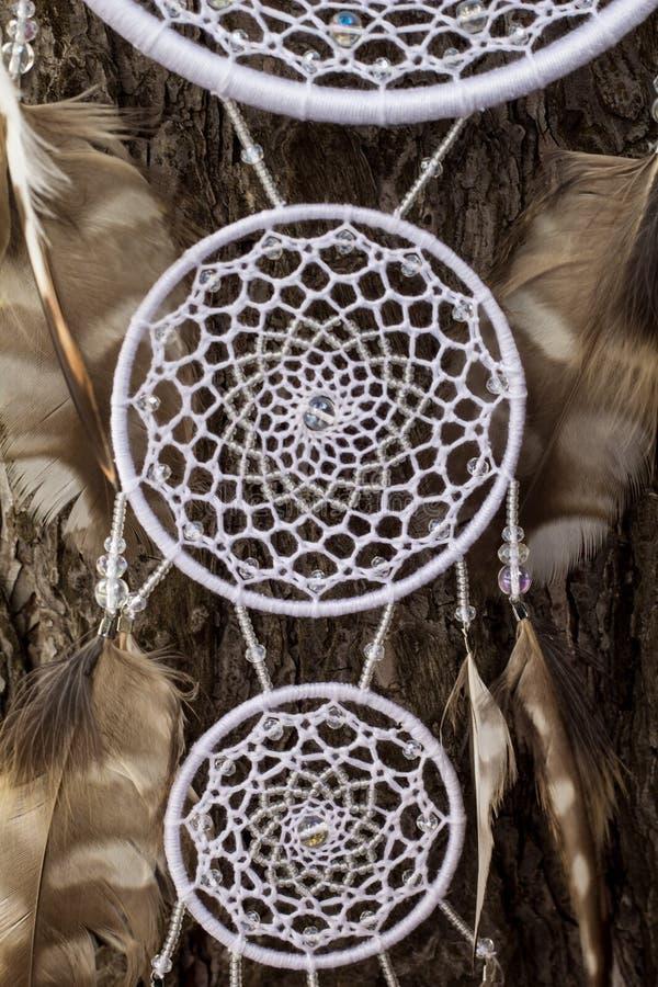 Den handgjorda dröm- stopparen med fjädrar dragar och pryder med pärlor att hänga för rep royaltyfria bilder
