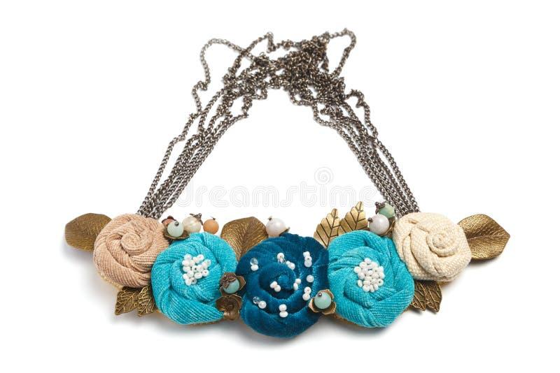 Den handgjorda halsbandet i form av flera blommor av cyan, blått och beiga färgar på en vit bakgrund arkivfoton
