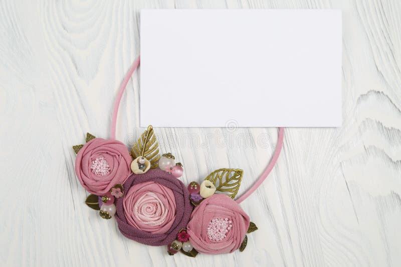 Den handgjorda halsbandet med färgade rosa färger blommar att ligga på en vit träbakgrund och bokstaven med lyckönskan arkivbilder