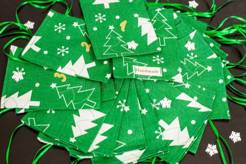 Den handgjorda juladventkalendern för barn, den gröna adventen numrerade säckar som var klara att fyllas upp med leksaker och god royaltyfria bilder