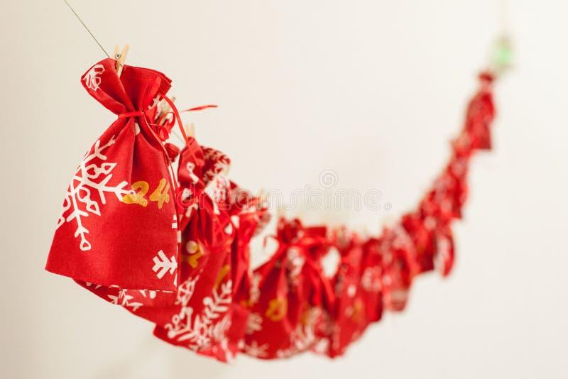 Den handgjorda juladventkalendern för barn, den röda adventen numrerade säckar som hänger på väntande på barn för vägg arkivfoto