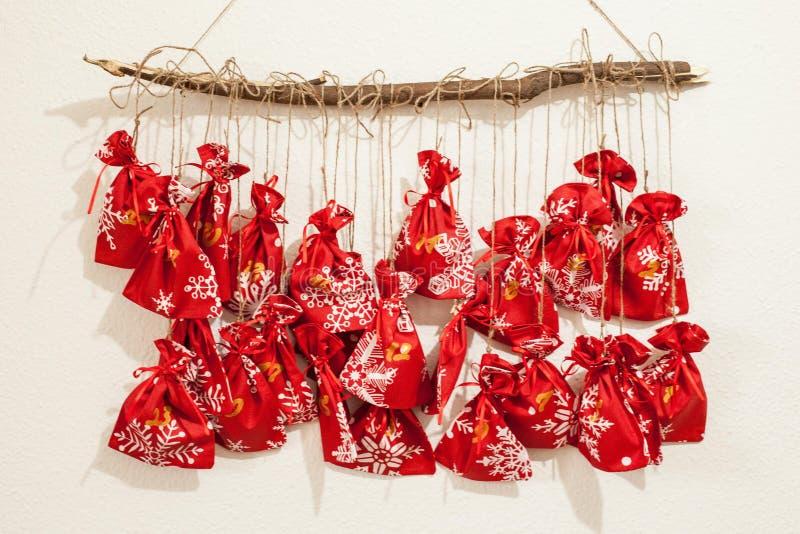 Den handgjorda juladventkalendern för barn, den röda adventen numrerade säckar som hänger på väntande på barn för väggen som ska  arkivfoton