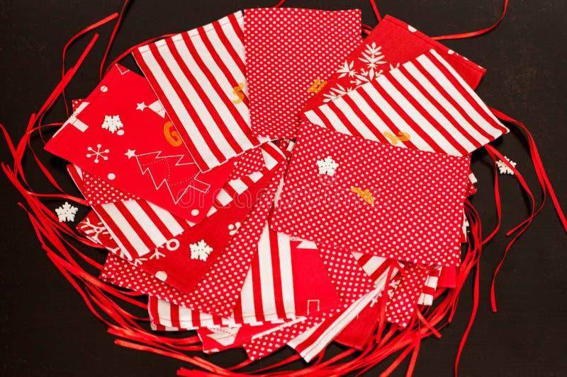 Den handgjorda juladventkalendern för barn, den röda adventen numrerade säckar som var klara att fyllas upp med leksaker arkivfoto