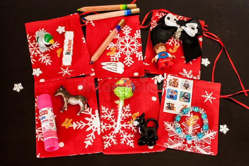 Den handgjorda juladventkalendern för barn, den röda adventen numrerade säckar som var klara att fyllas upp med leksaker royaltyfri fotografi