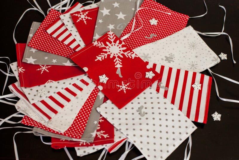 Den handgjorda juladventkalendern för röd, vit och grå adventen den barn, numrerade säckar som var klara att fyllas upp med leksa royaltyfri foto