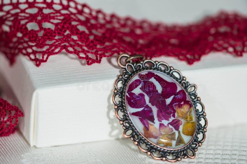 Den handgjorda tättsittande halsbandhalsbandet från snör åt och hängen med naturliga blommor arkivbild